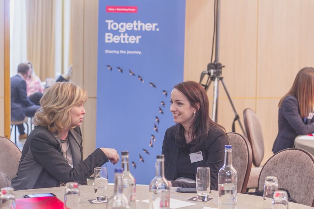 Two women talking at a table together in front of a banner with together better written on it
